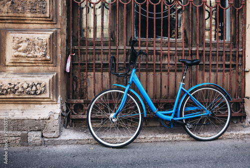 Plexiglas Fiets Vintage blue bike against old house, toned.
