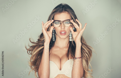 Young pretty woman with long hair in erotic bra standing in glasses on grey background - 211542796