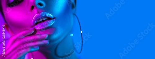 Wysokiej mody modela kobieta w kolorowych jaskrawych neonowych światłach pozuje w studiu. Piękna seksowna dziewczyna, modny świecące makijaż, metalowe srebrne usta