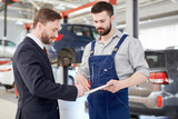 Waist up portrait of handsome businessman signing contract for car repairs while talking to modern mechanic in service garage - 211545709
