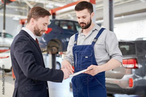 Waist up portrait of handsome businessman signing contract for car repairs while talking to modern mechanic in service garage