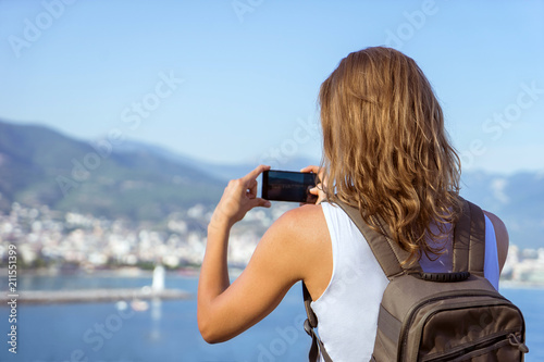 Fototapeta traveling woman making photo of cityview, travel concept, mounta