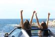 Leinwanddruck Bild - Joyful tourists watching the sea in a convertible car