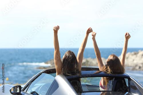 Leinwanddruck Bild Joyful tourists watching the sea in a convertible car