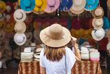 Young woman traveler looking for hat at the local market in Thailand - 211570374