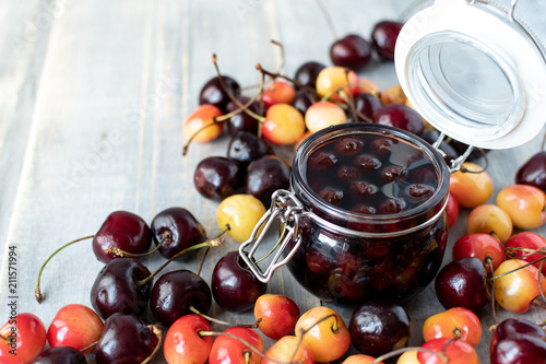 Aluminium Kersen cherry marmalade in a glass jar with a lid, a jar stands in red cherries, conservation for the winter. selective focus and copy space