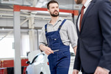 Portrait of modern bearded mechanic talking to unrecognizable businessman working across workshop in  car service and repair center, copy space - 211575104