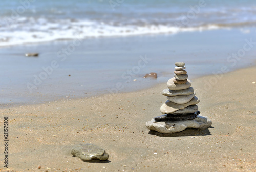 Pebbles piled on the sand in front of the sea  - 211575108
