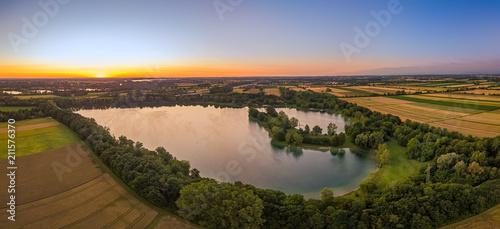 Der Feringasee in Unterföhring im Morgenrot des Sonnenaufgangs als Panorama aus der Luft /Aerial