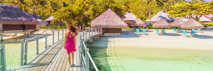 Luxury travel resort beach vacation destination in Bora Bora, Tahiti. Woman enjoying holidays relaxing in sun walking over water at bungalow rooms overwater villas.