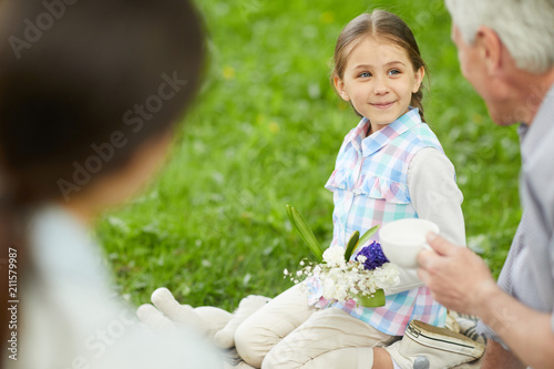 Cute little girl with floral bouquet looking at grandfather during talk by cup of tea on picnic