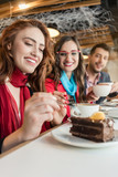 Low-angle view of a trendy young woman talking on mobile phone, while enjoying a cup of coffee with her friends or colleagues in a modern cafeteria - 211581336