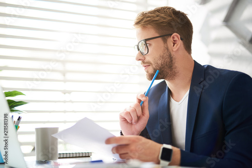 Leinwanddruck Bild Profile of handsome young male sitting at table and holding papers and blue pencil in hands. He is looking sideways absorbed in personal consideration of business ideas