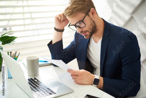 Side view of businessman concentrated on reading corporate papers at work. He is sitting at desktop with sheets in hand and touching head with hand. Coffee mug and laptop are aside