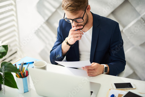Busy man sitting at desktop and holding papers in hand. He is checking them carefully and precisely   - 211581548