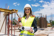 Portrait of a confident female architect or engineer with can-do attitude smiling while holding a rolled blueprint and a tablet on the construction site - 211582159