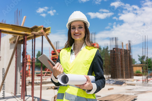 Leinwanddruck Bild Portrait of a confident female architect or engineer with can-do attitude smiling while holding a rolled blueprint and a tablet on the construction site