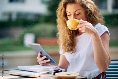 Poster Female student using tablet and drinking coffee in cafe. Books and notebooks on a table.
