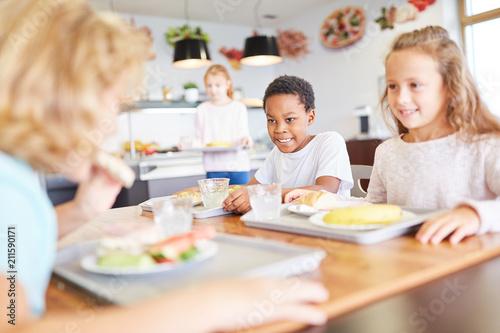Glückliche Kinder essen in der Kantine - 211590171