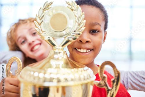 Junge zeigt stolz den Sieger Pokal - 211590329