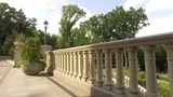 Architecture and buildings. Decorative stone handrails in an ornamental garden with green plants and flowers on a summer sunny day - 211596351