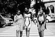 Three stylish african american womans walking on crosswalk or pedestrian crossing, speaking each other and having fun.