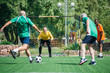 selective focus of multicultural elderly friends playing football together