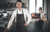 Professional barista in apron standing near coffee machines at cafe - 211604159