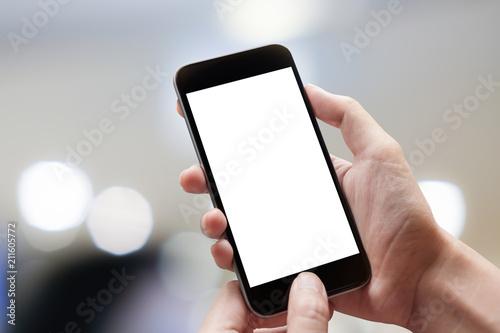 Leinwandbild Motiv Woman hand holding smartphone with blur bokeh. Blank screen mobile phone for graphic display montage