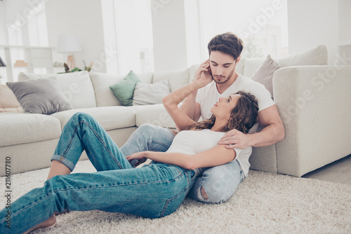 Leinwanddruck Bild Portrait of stylish trendy partners in denim clothes white t-shirts enjoying time together indoor sitting on floor. Understanding trust support leisure harmony idyllic concet