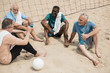 Leinwanddruck Bild - multiethnic smiling elderly volleyball players with sportive water bottles resting after game