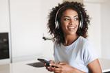 Delightened african woman in headphones