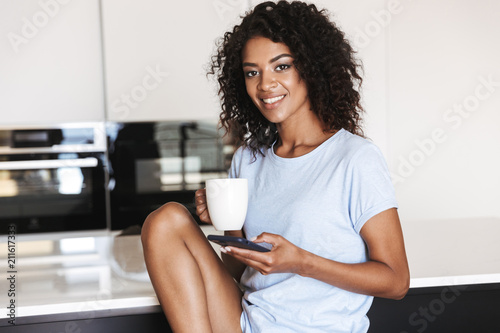 Satisfied african woman using mobile phone - 211617333