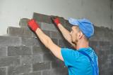 tiler installing ceramic tile panel in hall - 211618138