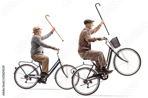 Seniors with canes riding bicycles with one of them doing a wheelie