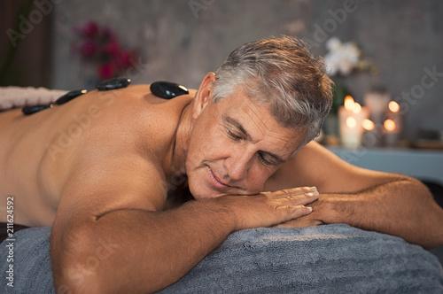 Starszy mężczyzna odpoczywa z gorącym kamiennym masażem