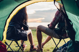 Young couple sitting discuss camping tent together