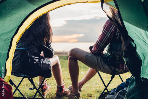 Leinwanddruck Bild Young couple sitting discuss camping tent together