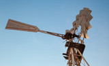 Vintage rusty wind motor under blue sky - 211627943
