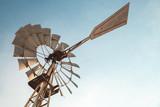 Vintage rusty wind motor under blue sky - 211627949