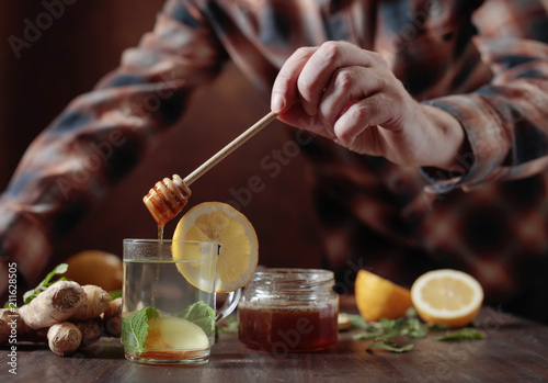 Fototapeta Ginger tea with honey , lemon and mint on old wooden table .
