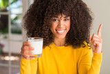 African american woman holding a glass of milk surprised with an idea or question pointing finger with happy face, number one