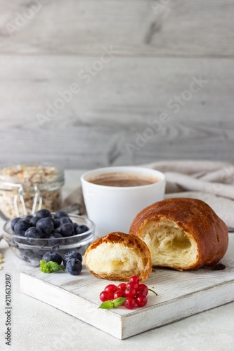 Poster Croissant with fresh berries, muesli and a cup of coffee or hot chocolate on a light background. Copy space