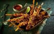 Dish full of spicy grilled seasoned satay skewers