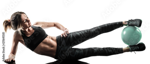 one caucasian woman exercising pilates fitness soft ball exercises isolated silhouette on white background - 211641581