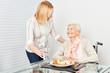 Pflegedienst Frau serviert alter Frau ein Essen - 211647125
