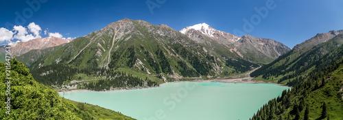 Plexiglas Khaki Amazing mountain lake panorama. Contrast colors of dark trees, frozen rocks and flower meadows. Kyrgyzstan.
