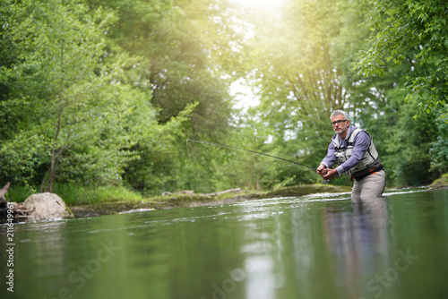 Leinwanddruck Bild Fisherman fly-fishing in river