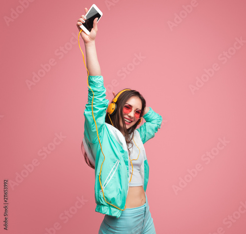 Young woman with smartphone dancing - 211653992
