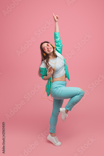 Woman listening to music and dancing in studio - 211654149